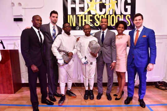 Two fencers pose with their coaches