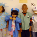Kids standing dressed as their future careers