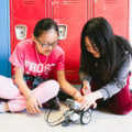 Two students use a robot in class