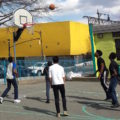 Kids playing some b-ball outside of the school