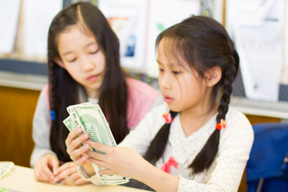 Two students at a desk counting play money.