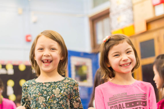 Two girls in a classroom smiling at the camera