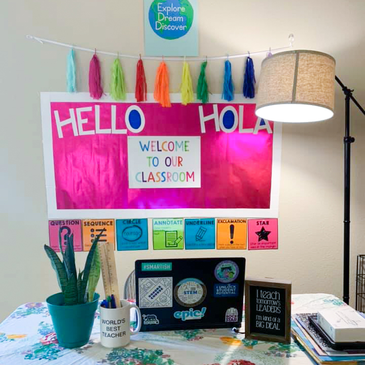 """A teacher's at-home teaching set up. It features a poster that says """"Explore, Dream, Discover"""" above another pink poster that says """"Hello, Hola, Welcome to our classroom."""" There's a desk below the posters, upon which there is a laptop, notebooks, and plants."""
